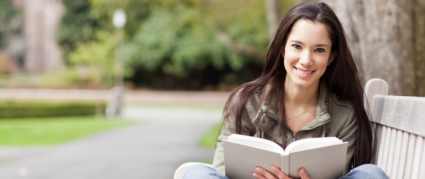 Female psychology student reading on park bench